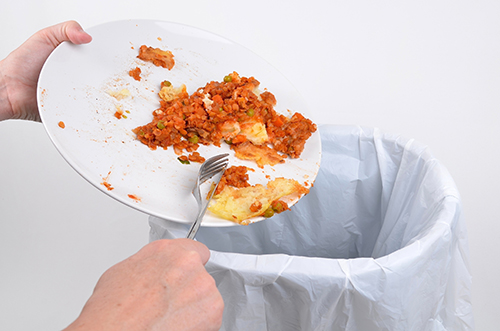 Scraping food into a household rubbish bin